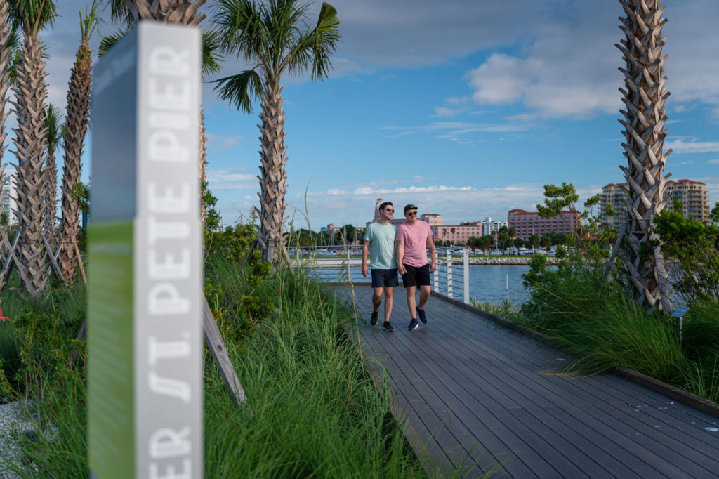 couple walking on pathway overlooking bay