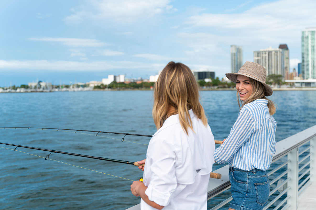 two women fishing off of pier