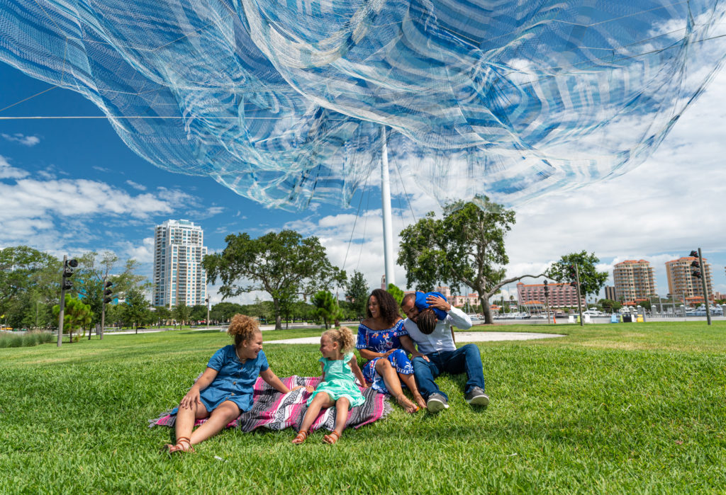 family sitting under net sculpture