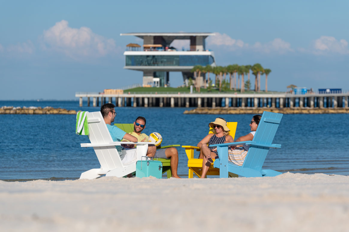 friends sitting in chairs on beach with pier in background